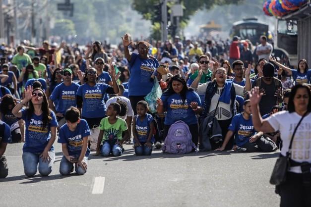 Fiéis se ajoelham participando de orações durante a Marcha para Jesus em São Paulo no feriado de Corpus Christi (Foto: Gabriela Biló/Estadão Conteúdo)